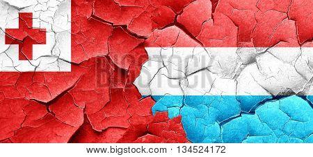 Tonga flag with Luxembourg flag on a grunge cracked wall