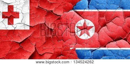 Tonga flag with North Korea flag on a grunge cracked wall