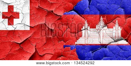 Tonga flag with Cambodia flag on a grunge cracked wall