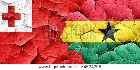Tonga flag with Ghana flag on a grunge cracked wall