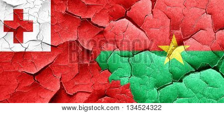 Tonga flag with Burkina Faso flag on a grunge cracked wall