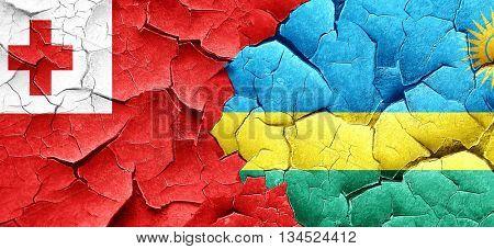Tonga flag with rwanda flag on a grunge cracked wall