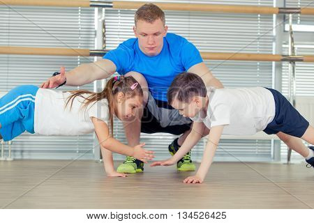 Group of children doing kids gymnastics in gym with nursery teacher.