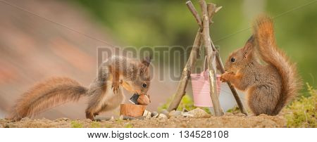 young red squirrels at a fire place with one squirrel holding a axe
