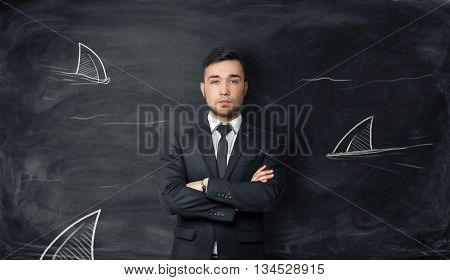 Businessman stands on background with sketches of shark fins. Symbol of fearlessness, sophisticated cunning, power and danger. Dangerous world of business and finance. Surrounded by enemies.