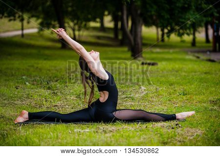 Beautiful young woman doing relaxing and stretching exercises in the park