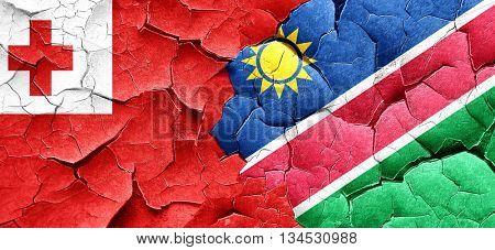 Tonga flag with Namibia flag on a grunge cracked wall