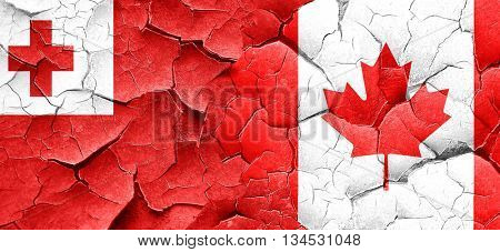 Tonga flag with Canada flag on a grunge cracked wall