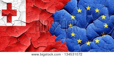 Tonga flag with european union flag on a grunge cracked wall