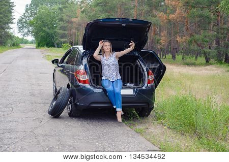 Young Beautiful Sexy Woman At Broken Car With Mobile Phone, Standing In The Public Road In Forest Ar