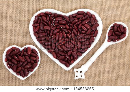 Kidney beans in heart shaped porcelain dishes and spoon forming an abstract background over hessian.