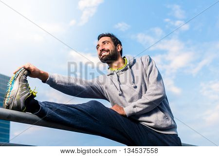 Man warming up for sport exercise in city