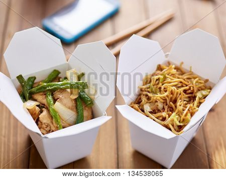 chinese take out food in boxes close up with mobile phone in background