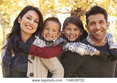 Portrait of happy parents piggybacking kids outdoors