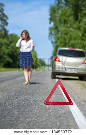 Woman calling to a car assistance after breakdown car on the roadside and red triangle warning sign. Focus on red sign