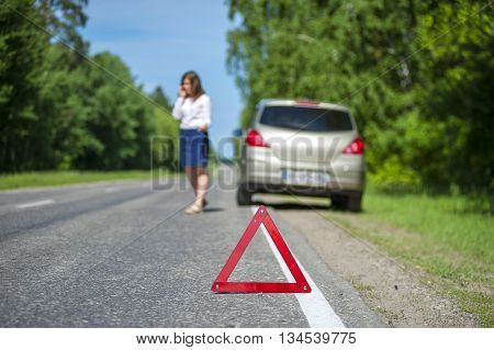 Red triangle warning sign female driver calling to a car assistance after breakdown. Focus on triangle.