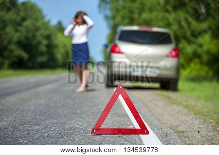 Woman talking on the phone near broken car red triangle warning sign closeup. Focus on red triangle.