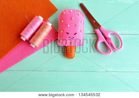 Hand cute felt ice cream toy. Pink wool ice cream with beading embroidery. Thread, needle, scissors, felt sheets. Creative sewing idea for kids summer vacation.