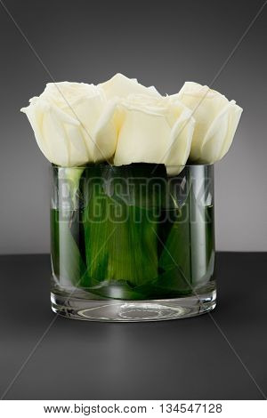 Bouquet of pink roses in glass vase, on a grey background