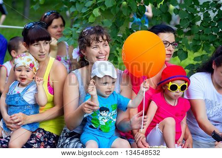 Zaporizhia/Ukraine- June 5, 2016: small children with mothers watching animation performance on charity family festival organized in regions with most quantity of refugees from Donetsk area, occasioned with International Children`s Day