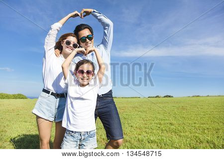 Happy playful young family forming love shape