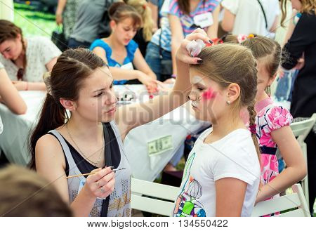 Zaporizhia/Ukraine- June 5, 2016: volunteer  painting cat mask on a girl`s face during charity family festival organized in regions with most quantity of refugees from Donetsk area, occasioned with International Children`s Day