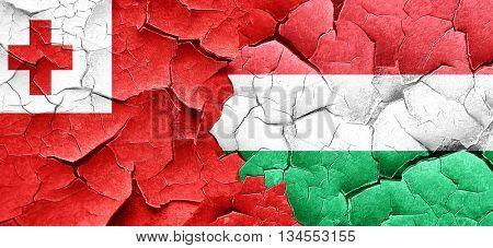 Tonga flag with Hungary flag on a grunge cracked wall