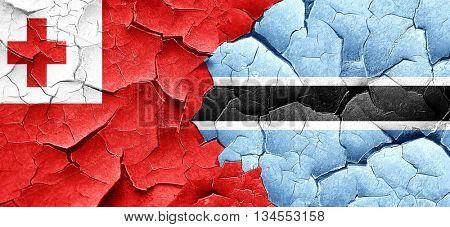 Tonga flag with Botswana flag on a grunge cracked wall