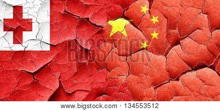 Tonga flag with China flag on a grunge cracked wall