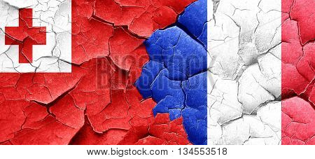 Tonga flag with France flag on a grunge cracked wall