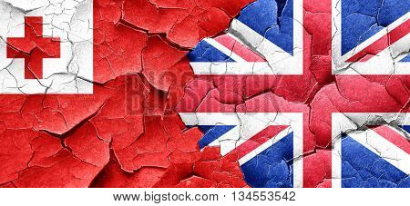 Tonga flag with Great Britain flag on a grunge cracked wall