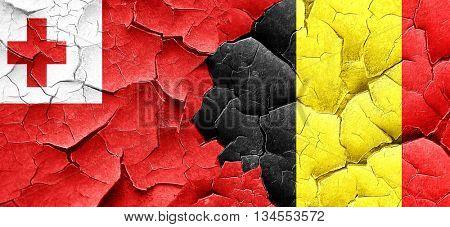 Tonga flag with Belgium flag on a grunge cracked wall