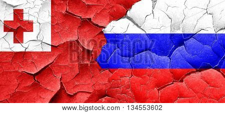 Tonga flag with Russia flag on a grunge cracked wall