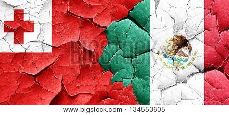 Tonga flag with Mexico flag on a grunge cracked wall