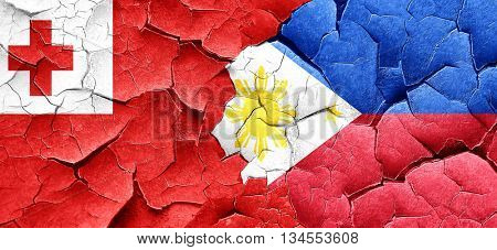 Tonga flag with Philippines flag on a grunge cracked wall