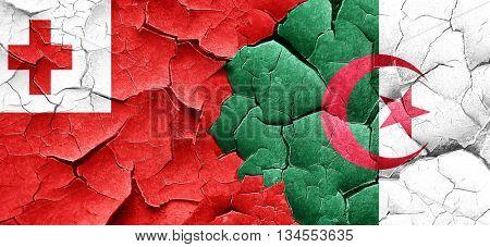Tonga flag with Algeria flag on a grunge cracked wall