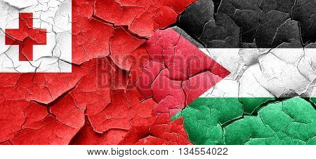 Tonga flag with Palestine flag on a grunge cracked wall