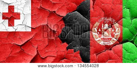 Tonga flag with afghanistan flag on a grunge cracked wall
