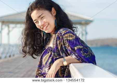 portrait asian woman long black hair with blue shawl and white jeans standing and smile at wood bridge Asdang in SICHANG island Thailand landmark