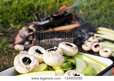Close up view of fresh mushrooms and zucchini in a metal pan waiting to be grilled on an outdoor barbecue with burning wood coals