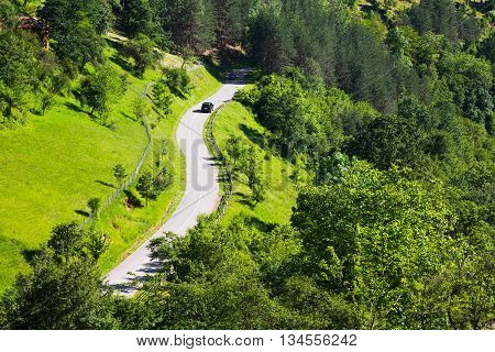 Aerial view of a car on a winding rural road through a scenic lush green forested mountain valley