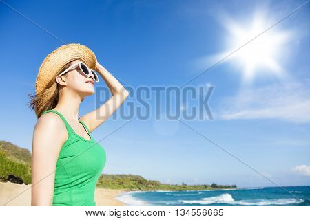 Young woman relaxing on the beach with sunlight background
