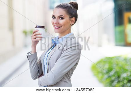 Businesswoman holding disposable cup outdoors