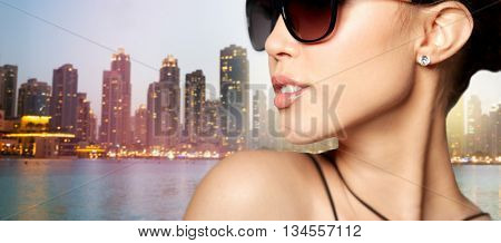accessories, eyewear, fashion, people and luxury concept - close up of beautiful young woman in elegant black sunglasses over dubai night city lights street background