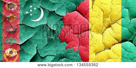 Turkmenistan flag with Guinea flag on a grunge cracked wall