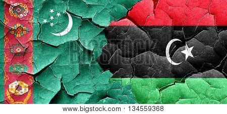 Turkmenistan flag with Libya flag on a grunge cracked wall