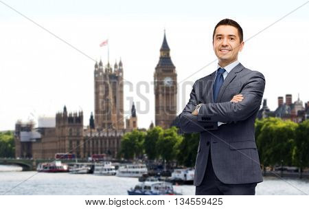 business trip, people and office concept - happy smiling businessman in dark grey suit over london city background