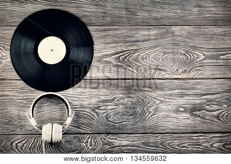 Vinyl record and headphones on a wooden wall