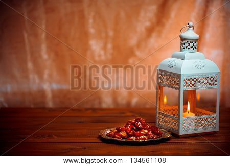 Beautiful Background With A Shining Fanus Lantern And Dried Dates On A Tray. The Muslim Feast Of The