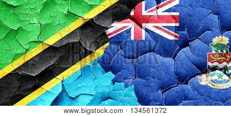 Tanzanian flag with Cayman islands flag on a grunge cracked wall